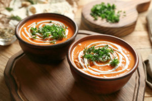 Two bowls of soup with herbs